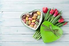 Tulipes et boîte-cadeau rouges avec des macarons Images stock