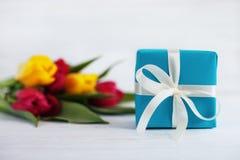 Tulipes et cadeau en bois blancs de fond Concept des vacances, BIR Photos stock