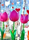 Tulipes et coeurs roses artificiels décoratifs contre le ciel bleu Image stock