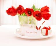 Tulipes et cuvette rouges de thé Photographie stock libre de droits