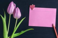 Tulipes et note de papier avec un coeur Image stock