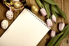 Tulipes et oeufs modifiés la tonalité de Pâques de fond Photographie stock