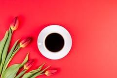 Tulipes et tasse de café sur le fond rouge Configuration plate, vue supérieure Photographie stock libre de droits