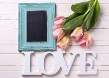 Tulipes fraîches de rose de ressort, amour de mot et tableau noir vide dessus Photo libre de droits