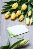 Tulipes jaunes et une carte de voeux vierge sur la table en bois Photographie stock libre de droits