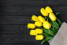 Tulipes jaunes lumineuses dans le sac de papier d'eco sur le vintage noir en bois merci Images libres de droits