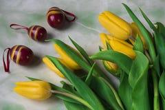 Tulipes jaunes néerlandaises avec les oeufs de pâques rouges blancs décoratifs photographie stock libre de droits