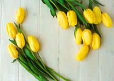 Tulipes jaunes sur une table en bois, fond de Pâques Images stock