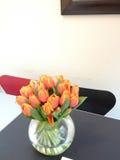 Tulipes oranges dans le vase à ampoule sur la table Images stock