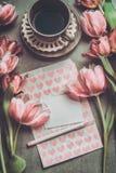 Tulipes pâles roses fraîches avec le coeur, le papier blanc, le marqueur et la tasse de café, vue supérieure Photos stock