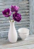 Tulipes pourpres dans un vase en céramique et une cuvette en céramique blanche sur un fond en bois bleu Image stock