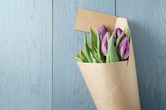 Tulipes pourpres en papier de métier sur le fond en bois bleu avec la vue supérieure de carte de papier Photos stock
