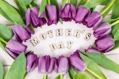 Tulipes pourpres pour le jour du ` s de mère sur les conseils blancs Images stock