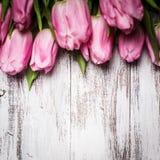 Tulipes roses au-dessus de table en bois Photographie stock