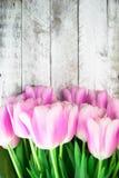 Tulipes roses au-dessus de table en bois blanche minable Photographie stock
