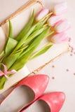 Tulipes roses avec des chaussures du ` s de femmes au-dessus de la table en bois blanche Ressort c Image stock