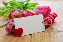 Tulipes roses avec la carte de coeur sur le fond en bois Photo stock