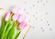 Tulipes roses avec le coeur et perles au-dessus de la table en bois blanche Closeu Photographie stock libre de droits