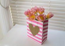 Tulipes roses dans un sac rayé de Valentine Images stock