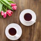 Tulipes roses sur le fond en bois, deux tasses de thé et café sur des soucoupes avec la confiture d'oranges de coeurs Images libres de droits