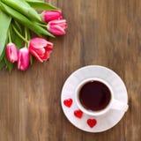 Tulipes roses sur le fond en bois, deux tasses de thé et café sur des soucoupes avec la confiture d'oranges de coeurs Photographie stock libre de droits
