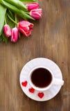 Tulipes roses sur le fond en bois, deux tasses de thé et café sur des soucoupes avec la confiture d'oranges de coeurs Image libre de droits