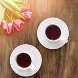 Tulipes roses sur le fond en bois, deux tasses de thé et café sur des soucoupes avec la confiture d'oranges de coeurs Photos stock