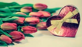 Tulipes rouges avec le cadeau de coeur d'isolement sur le fond blanc Image libre de droits