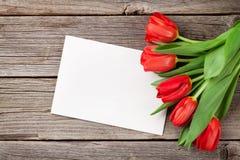 Tulipes rouges et carte de voeux de jour de valentines Photos stock
