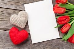 Tulipes rouges et carte de voeux de Saint-Valentin Images stock