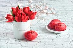 Tulipes rouges et oeufs de pâques rouges sur le fond criqué blanc Image stock