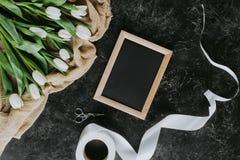 Tulipes, ruban et cadre blancs sur la surface noire, le 8 mars fond Photos libres de droits