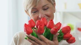 Tulipes sentantes de mère d'une cinquantaine d'années, souriant heureusement, rides sur le plan rapproché de visage clips vidéos