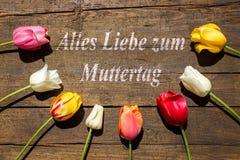Tulipes sur le fond en bois et le texte allemand pour le jour des motherPhoto libre de droits