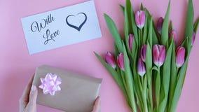 Tulipes sur le fond rose Femme mettant la carte de voeux avec le texte AVEC L'AMOUR et un cadeau Directement au-dessus de la vue banque de vidéos