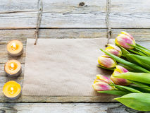Tulips and blank note on wooden background with candles. Fresh tulips and blank note on wooden background with candles Royalty Free Stock Photography