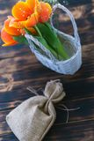 Tulips blooming in a basket on a wooden background stock images
