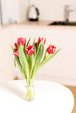 Tulips bouquet in glass on kitchen table Stock Photography
