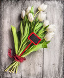 Tulips bouquet with red sign and ribbon on gray wooden background Royalty Free Stock Images
