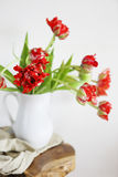 Tulips bouquet in white vase on wooden rustic chair Stock Photography