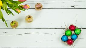 Tulips, bunnies and eggs on wooden background stock images