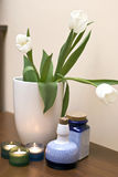 Tulips and candles. Home decoration consisting of white tulips in a vase, small candles and blue vases Stock Photos