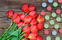 Tulips and candles. Bunch of fresh red tulips lying alongside of colorful candles on Valentines Day or an anniversary, overhead view Royalty Free Stock Images