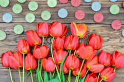 Tulips and candles. Bunch of fresh red tulips lying alongside of colorful candles on Valentines Day or an anniversary, overhead view Stock Photography