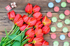 Tulips and candles. Bunch of fresh red tulips lying alongside of colorful candles on Valentines Day or an anniversary, overhead view Royalty Free Stock Photos