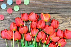Tulips and candles. Bunch of fresh red tulips lying alongside of colorful candles on Valentines Day or an anniversary, overhead view Stock Image