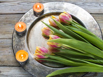 Tulips and candles. On a copper tray Royalty Free Stock Photo