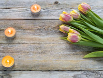 Tulips and candles on the wooden table. Place for text Stock Photo