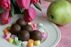 Tulips, Candy and Fruit. A romantic still life with pink tulips, a pear and some milk chocolates and candy hearts on an ivory plate Stock Images