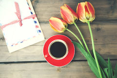 Tulips,coffee and letter. On wooden table Royalty Free Stock Photos